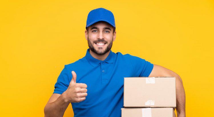 Entregador dos Correios carregando encomendas em caixas de papelão, compradas com a funcionalidade de correios barato da Frenet