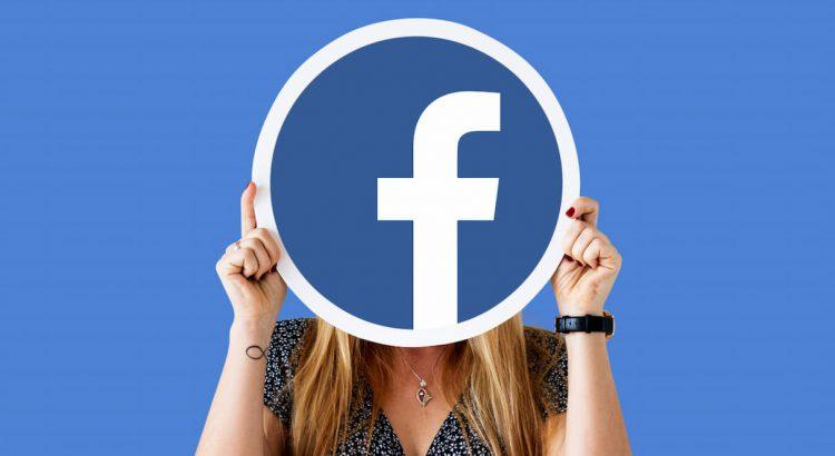 Uma mulher segurando um cartaz com o logotipo do facebook, representando a criação de uma copy para anúncios do facebook