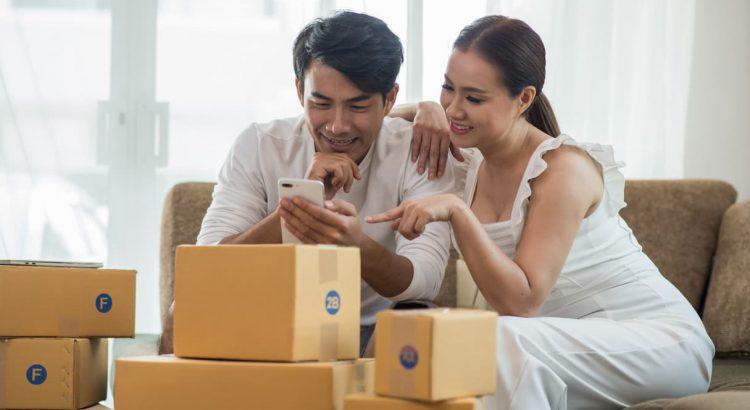 Casal de lojistas acompanhando suas vendas cercados de caixas de encomendas, um exemplo de regras de frete para loja virtual