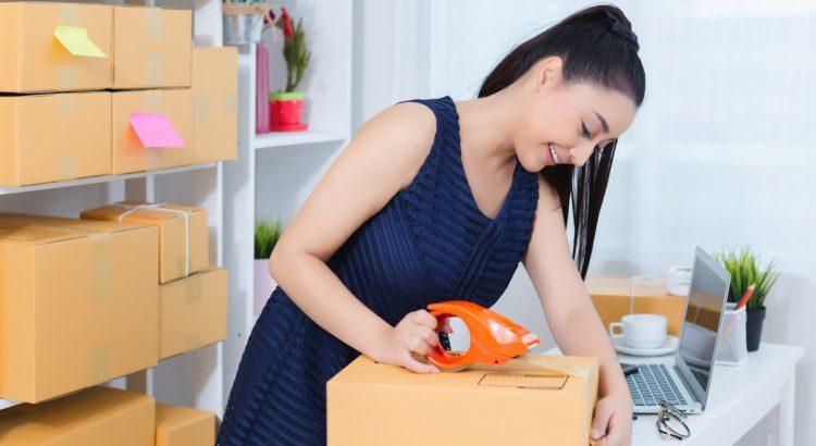 Mulher lojista embalando um produto pronto para entrega em seu ambiente de trabalho