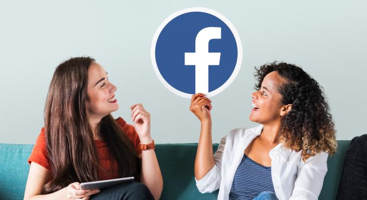 Mulheres sentadas em um sofá e olhando para o logotipo do facebook