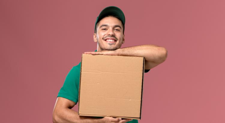 Entregador sorrindo e segurando uma caixa de entrega com as duas mãos