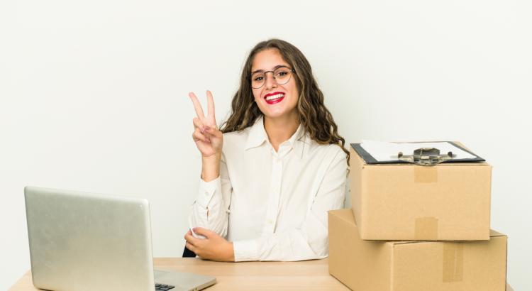 Mulher lojista feliz em seu escritório com um computador e caixas em cima de sua mesa